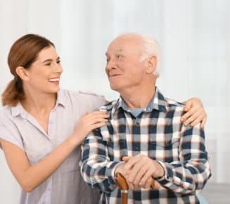 caregiver and senior man looking at each other while smiling