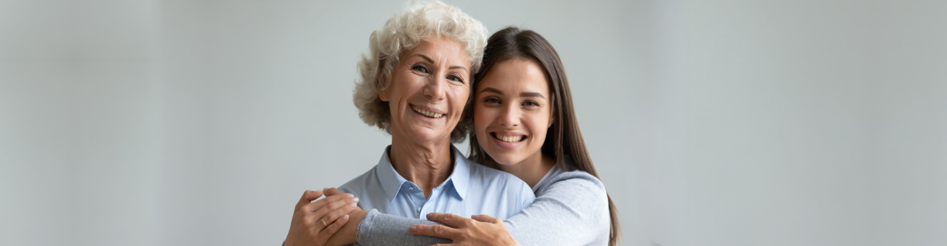caregiver hugging senior woman from the back